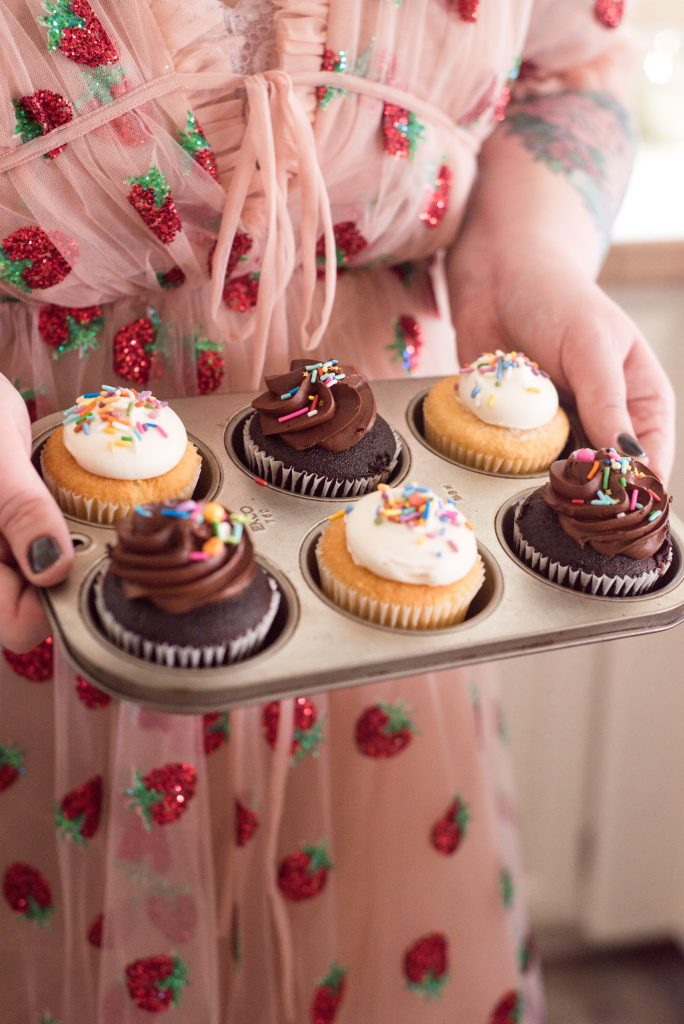 author holding tray of cupcakes