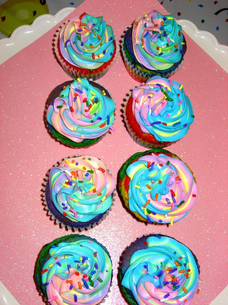 Eight rainbow cupcakes lined up in two columns of four on a red background