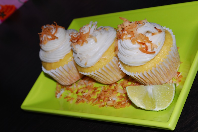Three pina colada cupcakes on a lime green plate with a slice of lime