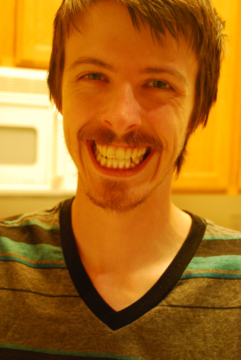 A white male with brown hair smiling at the camera