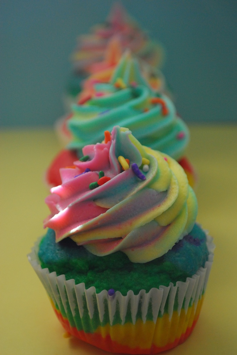 Multiple rainbow cupcakes lined up in a row on a yellow and blue background