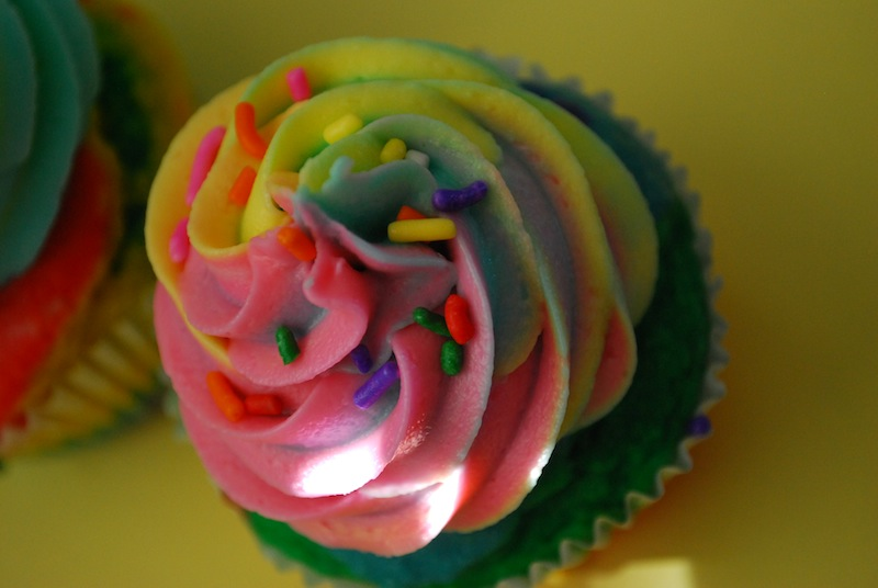 Close-up of a rainbow cupcake with rainbow frosting on a yellow background