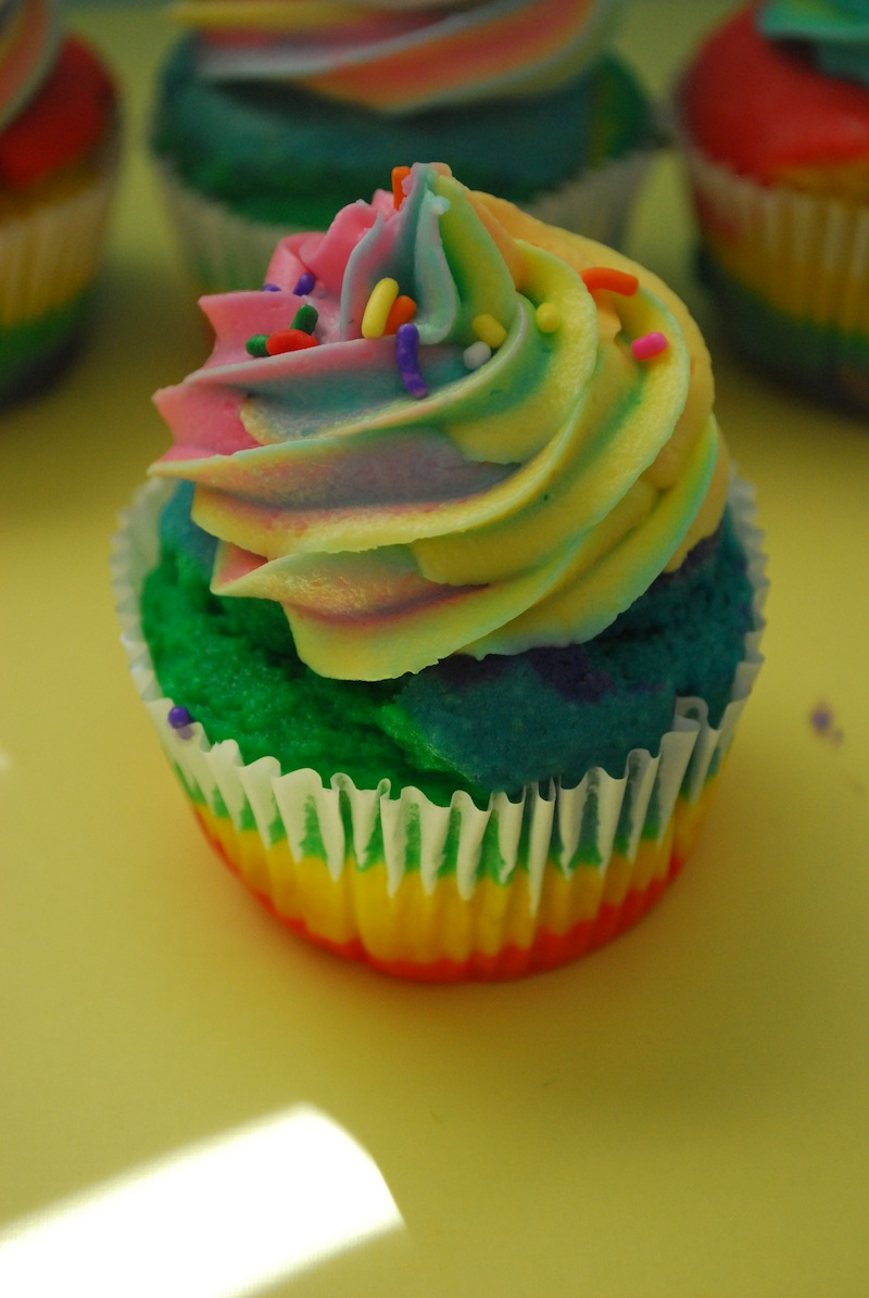 One rainbow cupcake in front of a few others on a yellow background