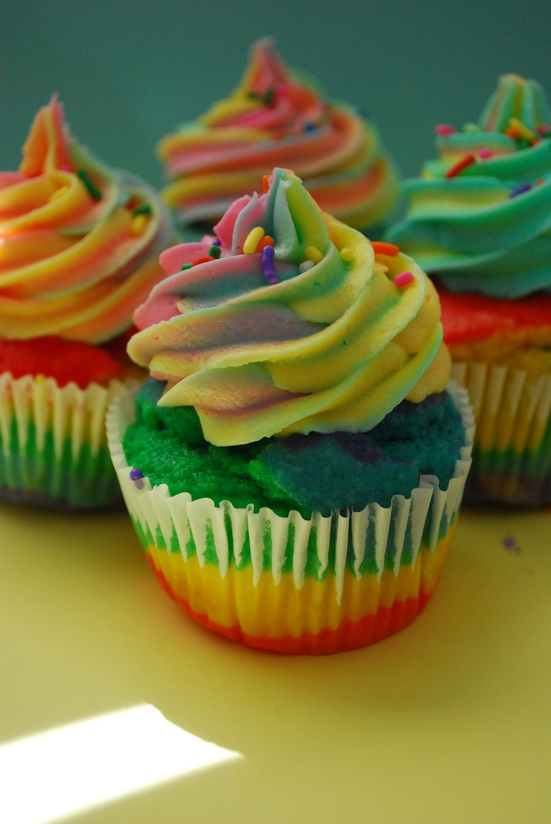 Four rainbow cupcakes on a yellow and blue background