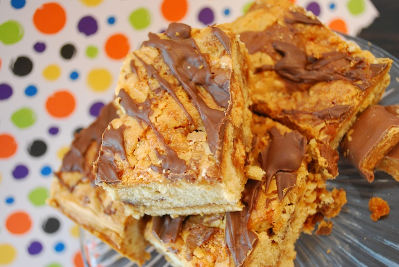 Butterfinger blondies on a clear platter in front of a polka dot background