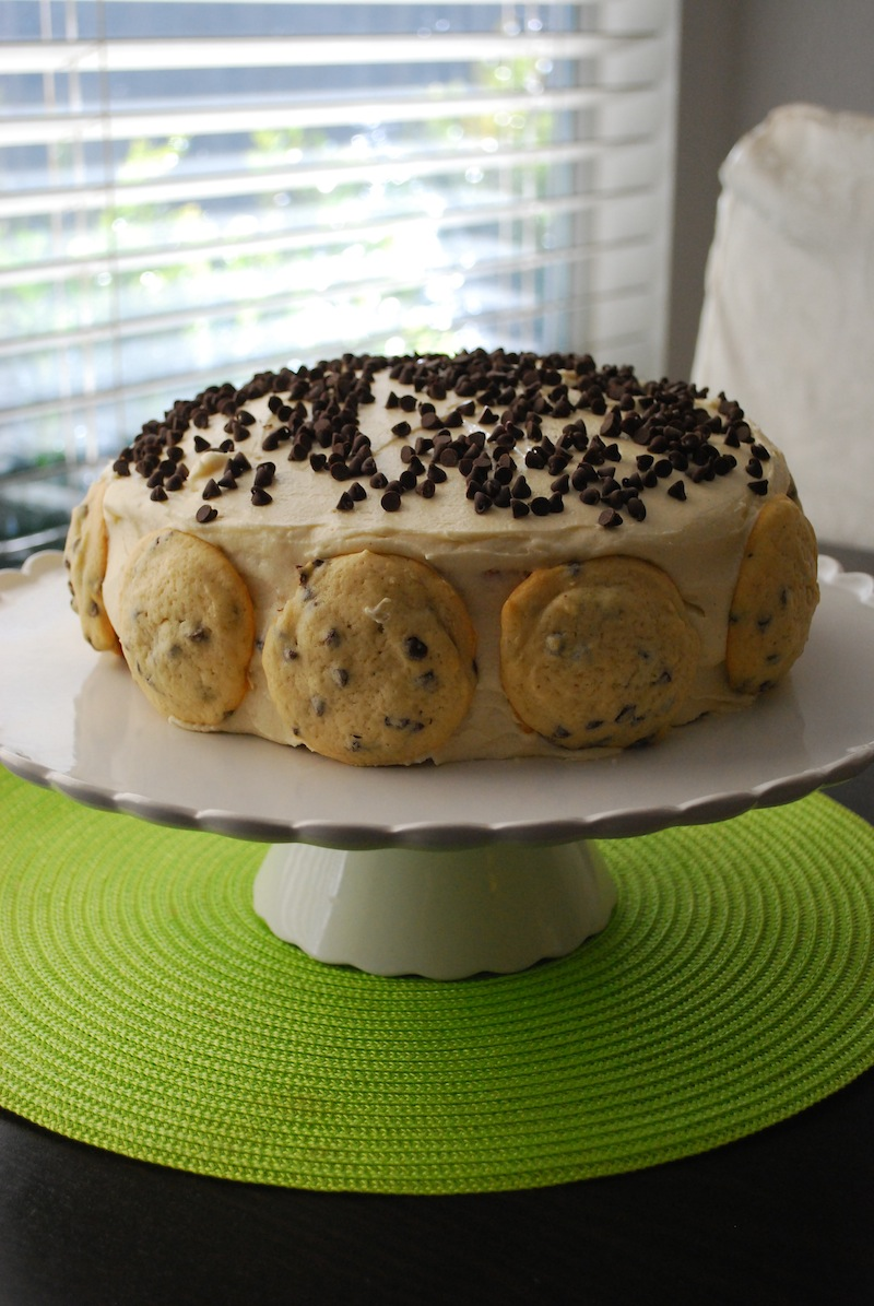 chocolate chip cookie dough cake on a cake stand in front of a window