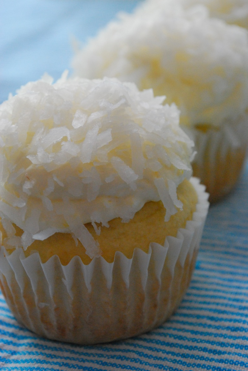 Close-up of lite triple coconut cupcakes on a blue and white striped background