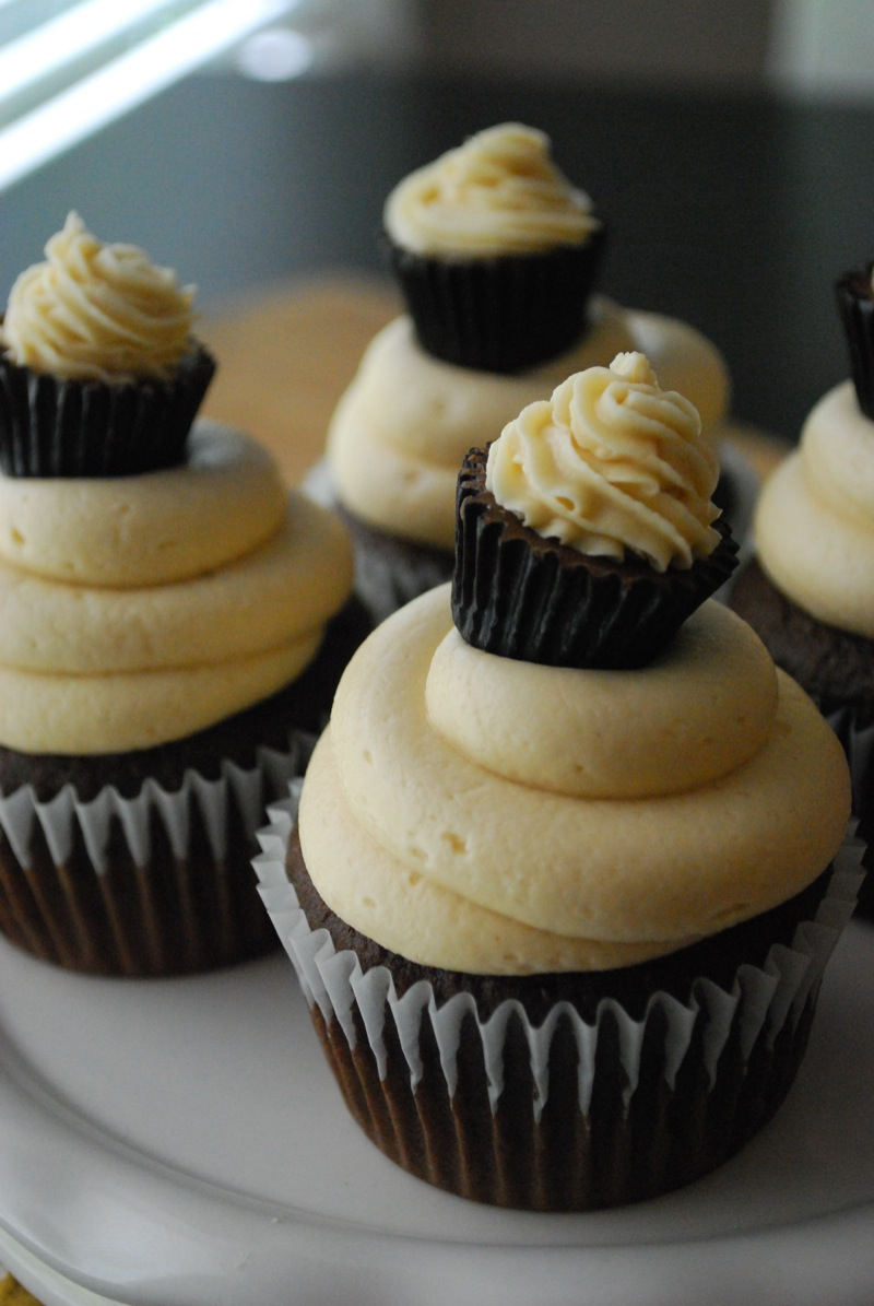 A few chocolate peanut butter cupcakes sitting on a white plate