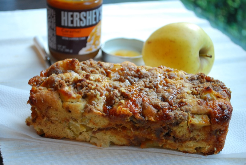 a caramel apple bread loaf with an apple and caramel sauce in background