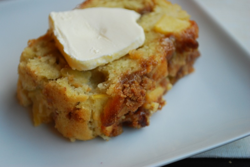 a slice of caramel apple bread with a pat of butter on a white plate