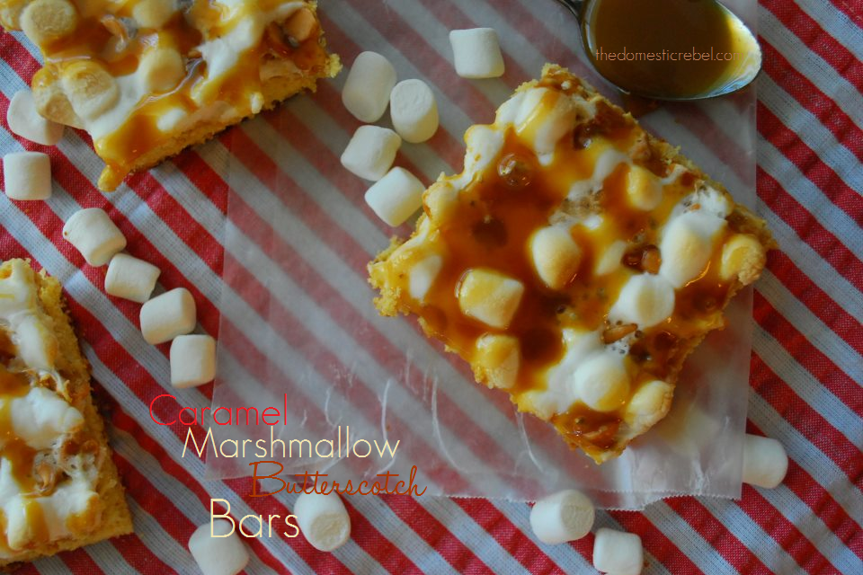 caramel marshmallow butterscotch bars arranged on parchment and red striped fabric with marshmallows