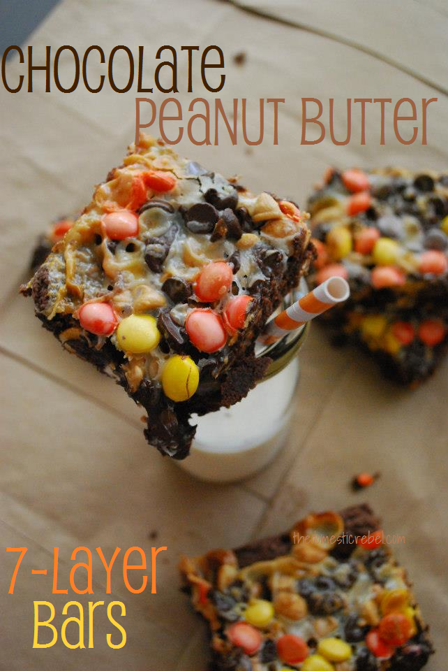 chocolate peanut butter seven layer bars sitting on a glass of milk on brown background