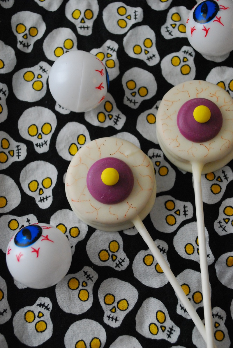 Eyeball oreo pops sitting on skull fabric with plastic eyeballs