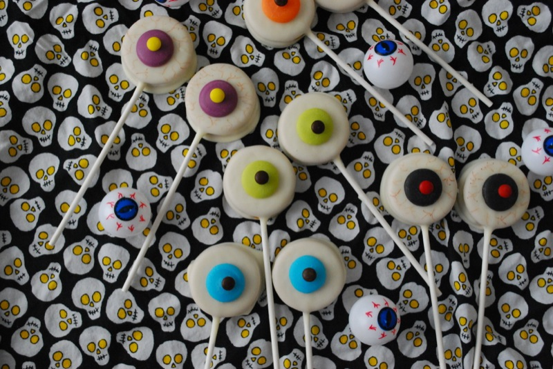 An assortment of eyeball Oreo pops on skull print fabric