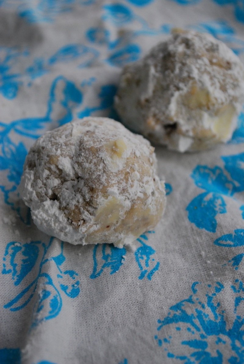 Two pecan snowball cookies on a blue and white cloth
