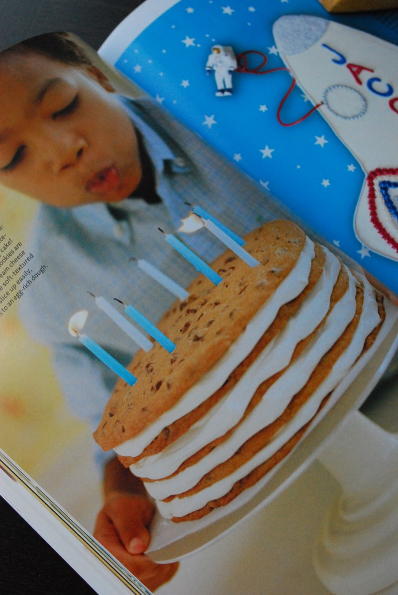 photo from a magazine of a child blowing out candles on a cookie cake