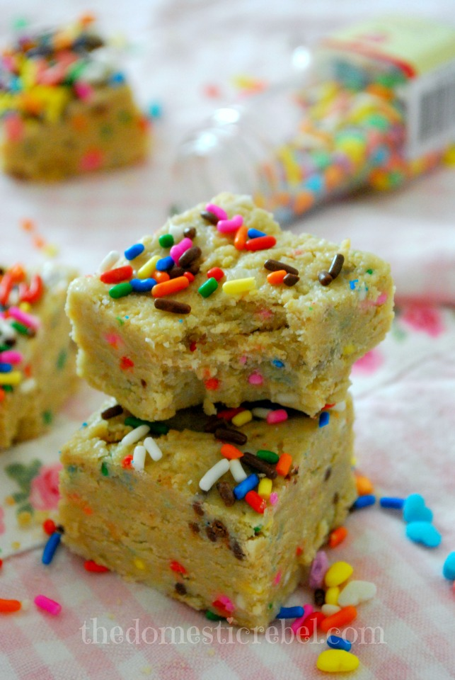 no bake cake batter squares stacked with a bite removed