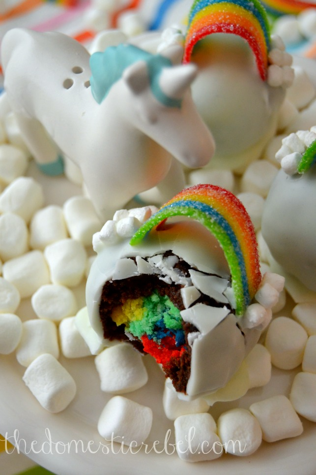 over the rainbow brownie bombs with bite removed and unicorn figurine on bed of marshmallows