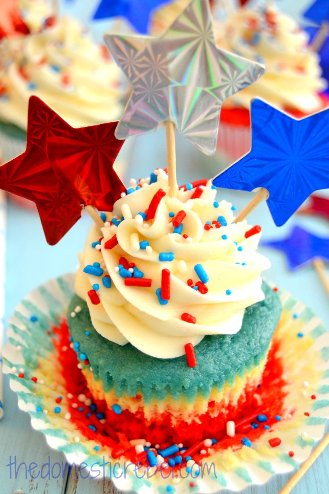 patriotic tie dye cupcake up close with star toothpicks on blue background
