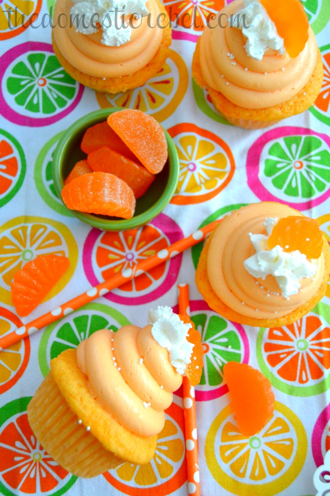 orange creamsicle cupcakes arranged on bright dishtowel with orange candies