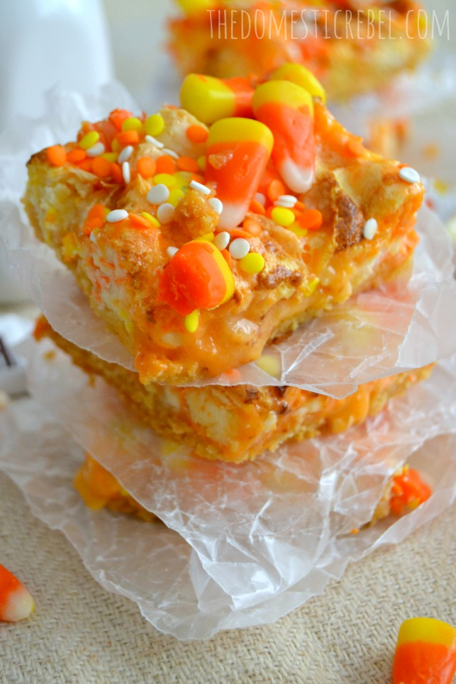 candy corn magic bars stacked between pieces of parchment on light background
