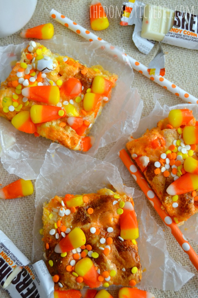 candy corn magic bars arranged on parchment squares on light background with candy