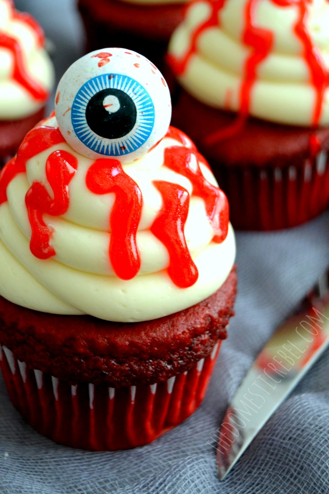 bloody eyeball halloween cupcakes closeup with knife on grey fabric