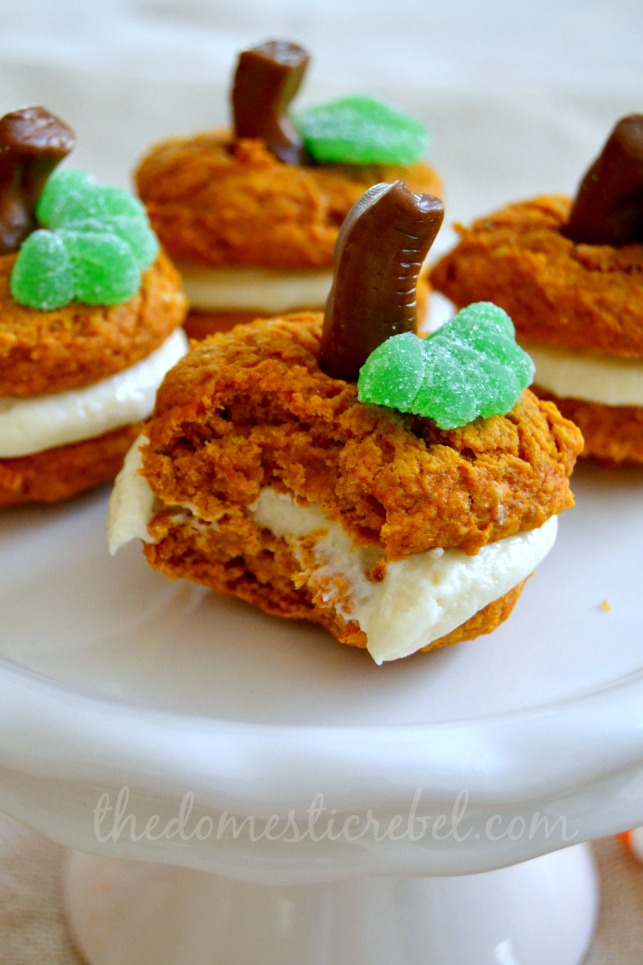 pumpkin whoopie pies with bite mark on white stand