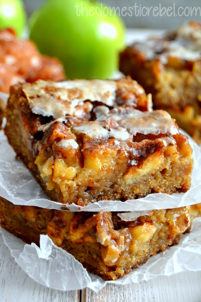 apple fritter blondies stacked between parchment paper with apples in background