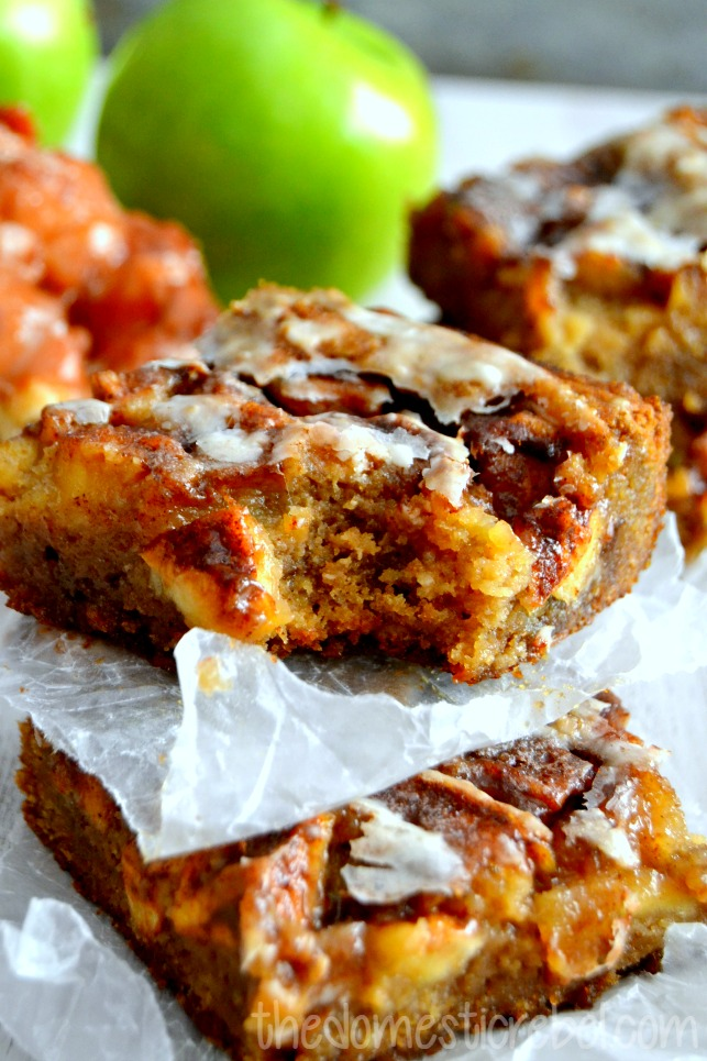 apple fritter blondies stacked between parchment with a bite mark and green apple in background