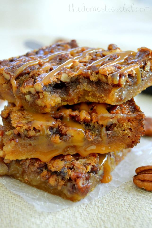 salted caramel pecan pie bars stacked with a bite mark on light fabric