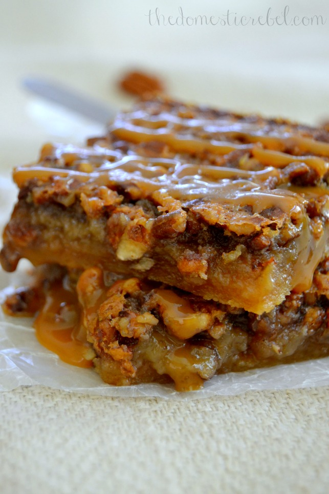 salted caramel pecan pie bars stacked on a light fabric
