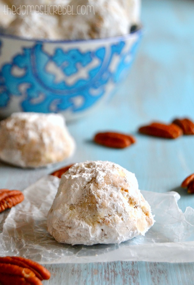 The Best Snowball Cookie on a piece of parchment with pecans and a bowl of cookies in background
