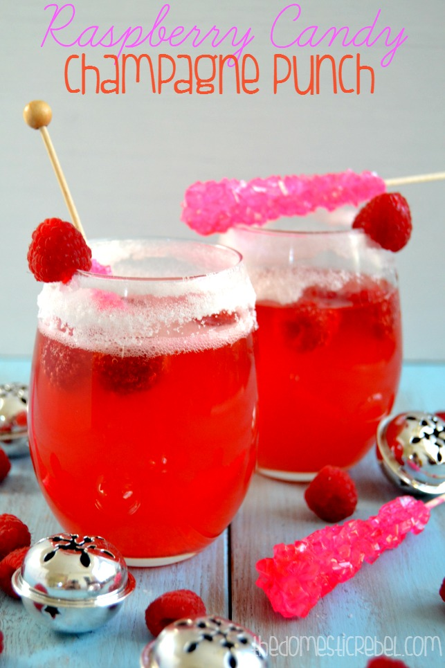Raspberry Candy Champagne Punch in 2 glasses with rock candy stirrers and bells in background