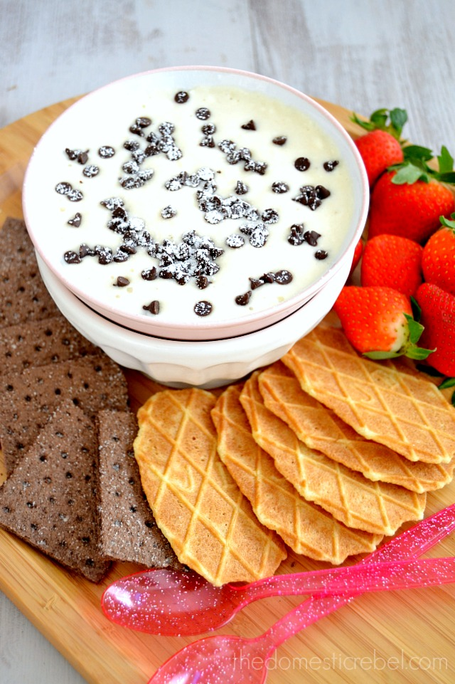 Creamy Cannoli Dessert Dip surrounded by assorted cookies and fruits on wood background