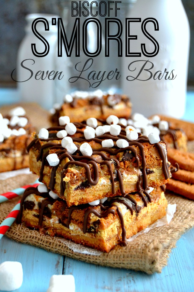 Biscoff Smores Seven Layer Bars stacked on burlap and blue background