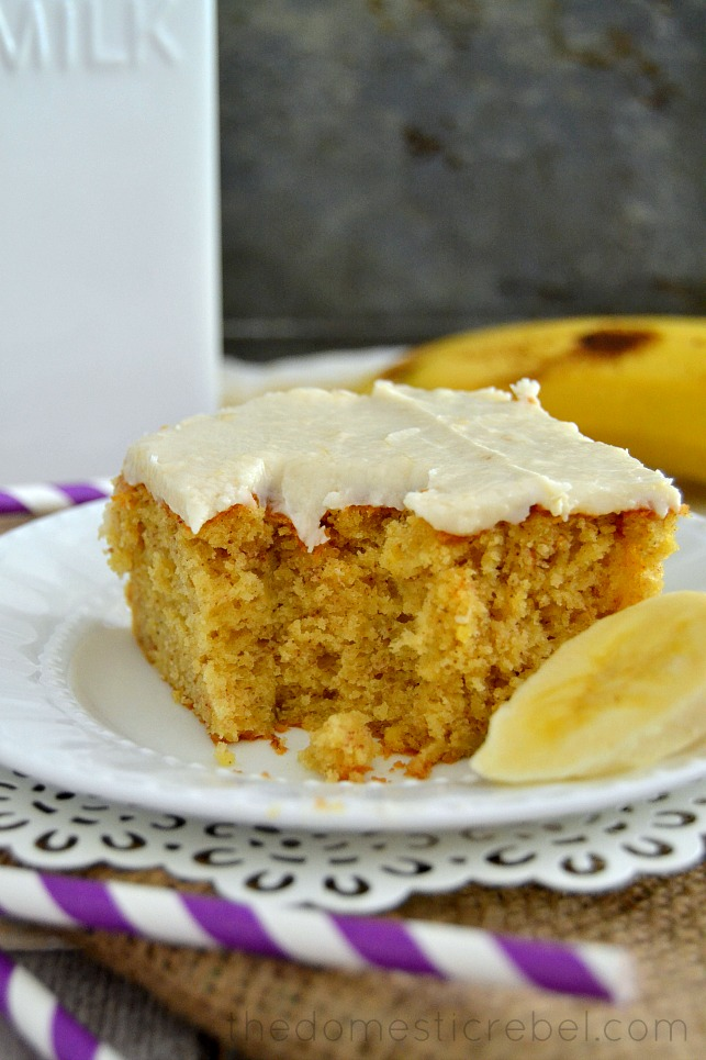 Best Banana Cake with Banana Frosting on white plate with banana slices with bite removed