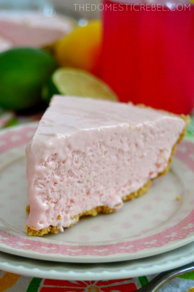 closeup of pink lemonade cheesecake pie on pink plate with limes and pink lemonade in background