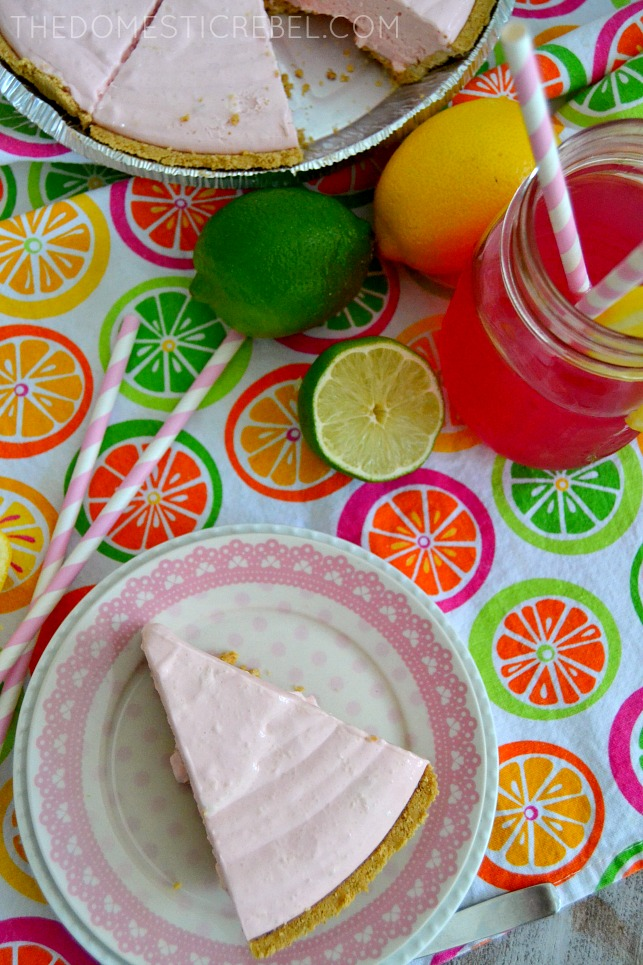 pink lemonade pie on plate with limes, pink lemonade and straws on bright fabric