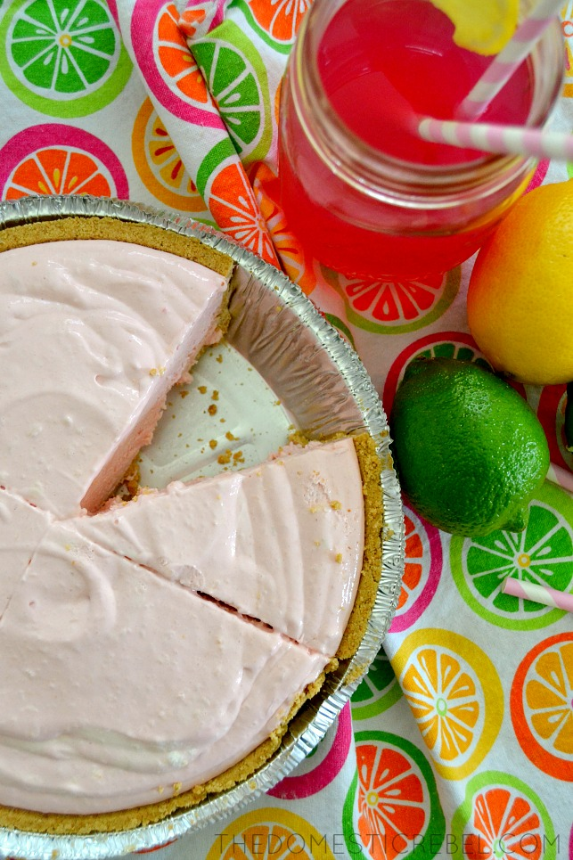 shot of pink lemonade cheesecake pie in pie pan with citrus and pink lemonade in background