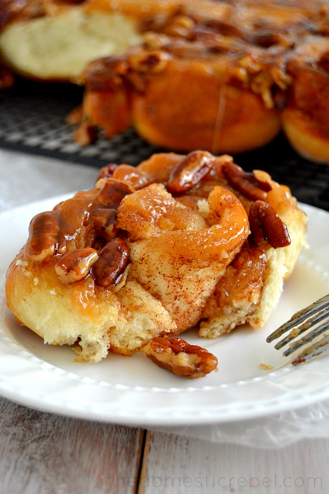 pecan sticky bun on white plate with fork and more sticky buns in background