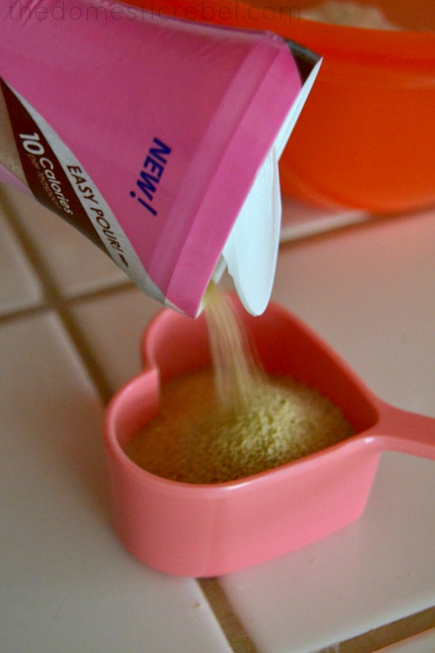 photo of sugar being poured into a heart shaped measuring cup