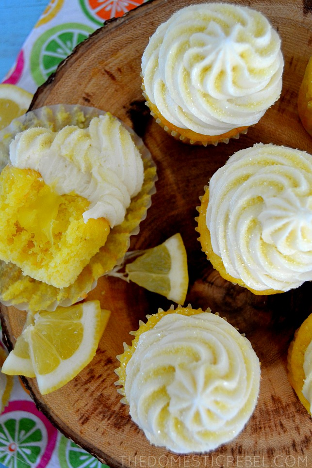 aerial view of lemon bar cupcakes arranged on wooden stand with lemon wedges