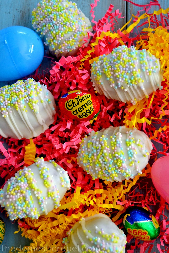 cadbury creme egg brownie bombs arranged with candies and plastic eggs on colorful paper shreds