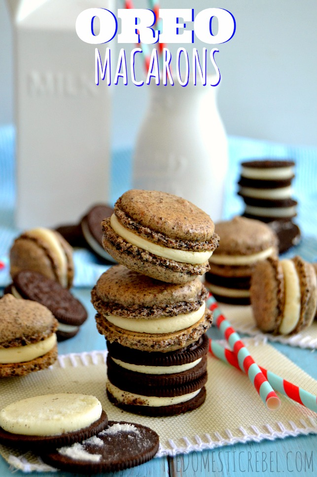 Oreo Macarons arranged on blue background with oreo cookies and milk glasses