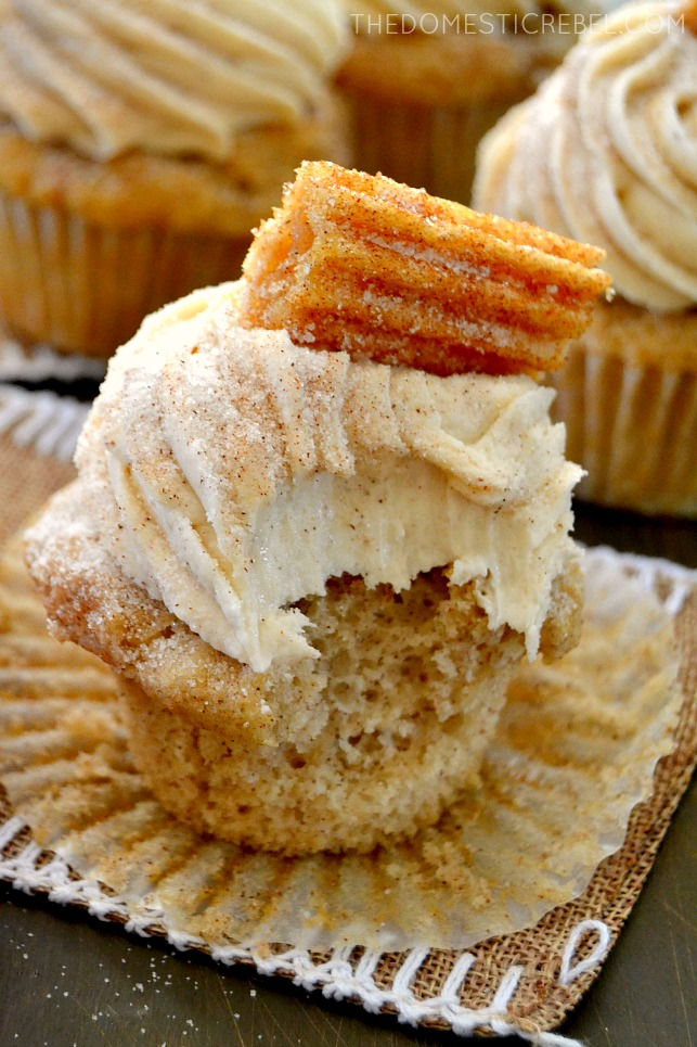 Churro Cupcake with bite removed on wood and burlap