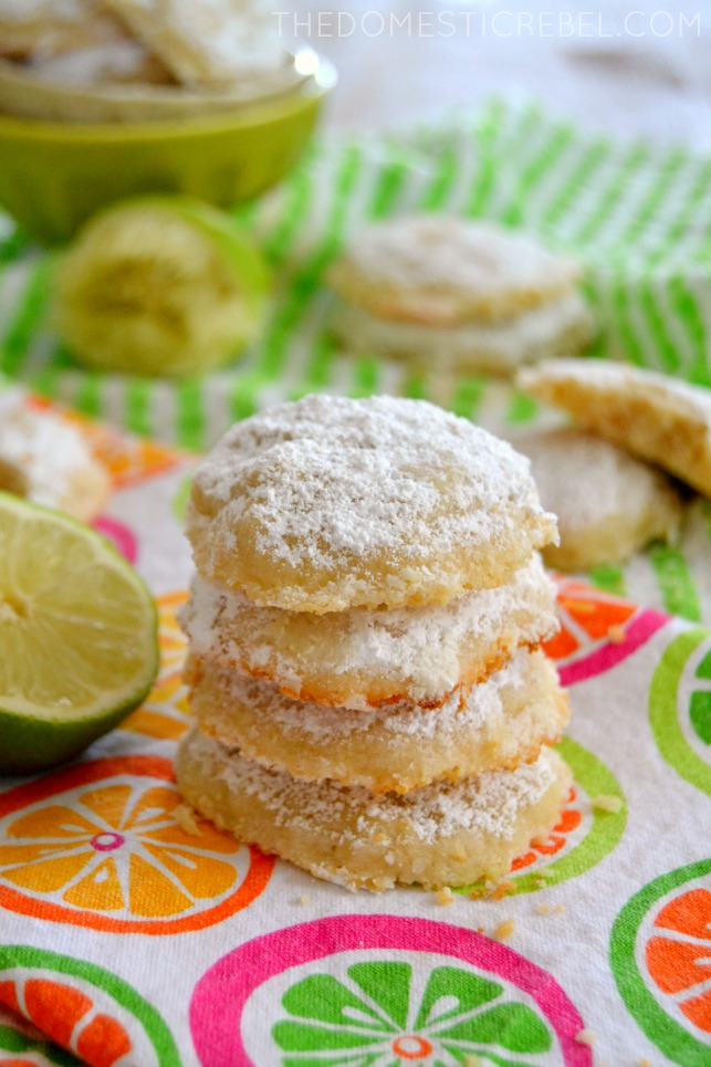 lime cooler cookies stacked on bright fabric with fresh limes