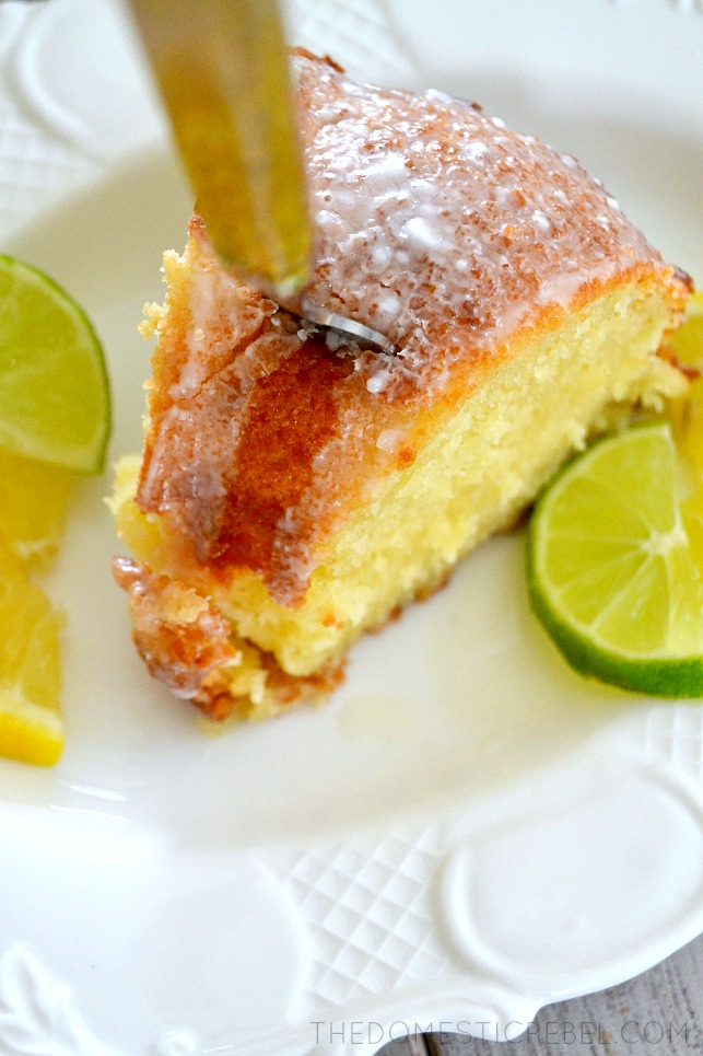 7Up Pound Cake on white plate with fork in it and fresh citrus