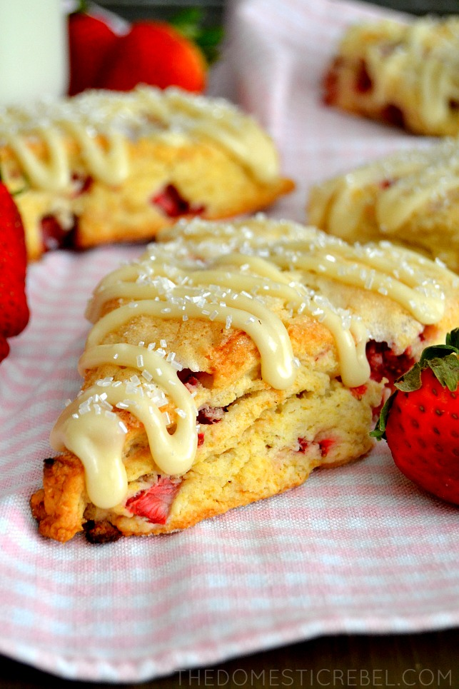 strawberry and cream scones scattered on pink fabric with fresh strawberries