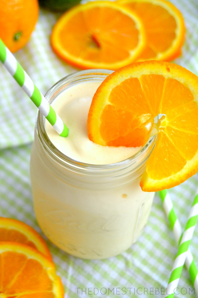 copycat orange julius drink in jar with fresh orange slices and a green straw